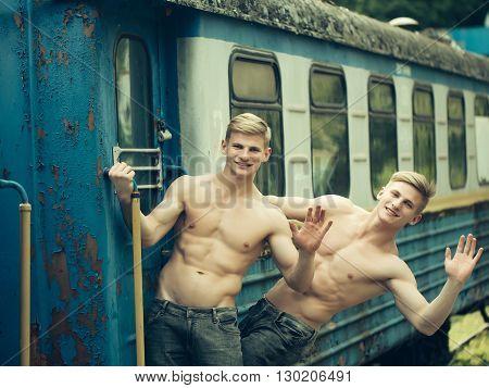 Muscular Guys Near Railway Train