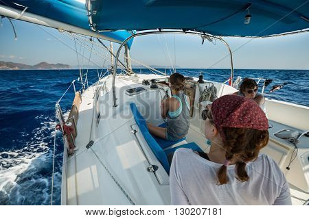 Group of young friends sailing in a blue sea