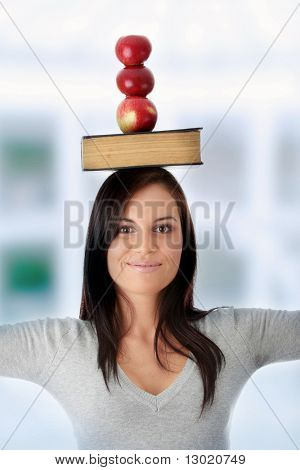 Beautiful student woman have book and apple on her head - learning concept