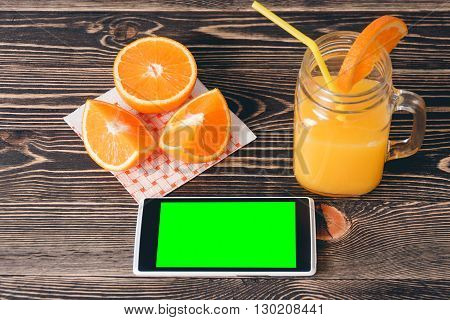 Oranges, Juice and Mobile Phone on Wooden Table. Technology Concept