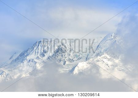 view of Mont Blanc through the clouds in winter