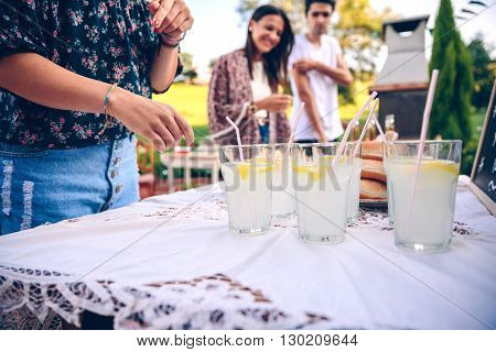 Young friends at table with fresh lemonade having fun in a outdoors summer barbecue