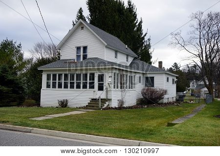 HARBOR SPRINGS, MICHIGAN / UNITED STATES - DECEMBER 24, 2015: A white home on Fourth Street in Harbor Springs.