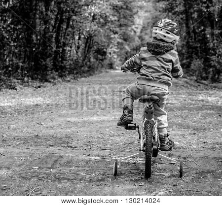 child riding a bicycle in the woods. Black and withe