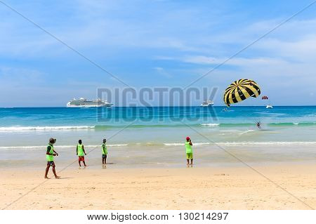 Young people walking on the beach, doing water sports.