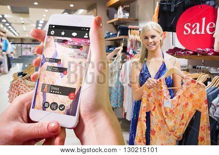 Hand holding smartphone against woman holding up orange shirt