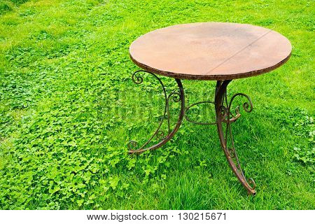 one old table from rusty iron is located separately on a lawn for a natural vintage interior
