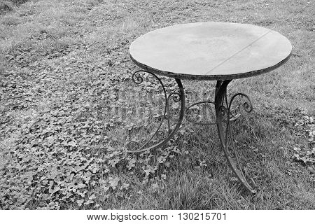 one old table from rusty iron is located separately on a lawn for a natural vintage interior of monochrome tone