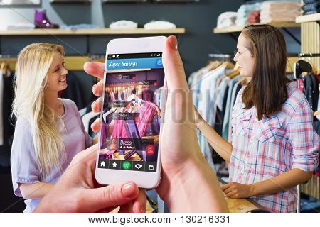 Hand holding smartphone against smiling blonde doing shopping