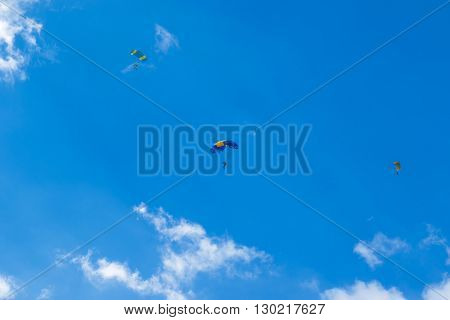 Three skydivers with open parachutes floating in the blue sky with clouds