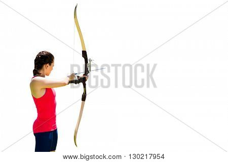 Side view of woman practicing archery against white background