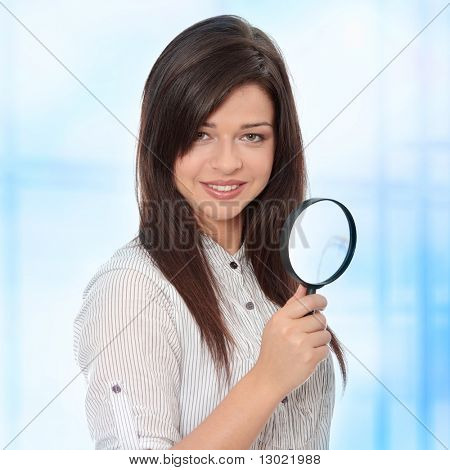 Young attractive smiling business woman looking into a magnifying glass. Over abstract blue background
