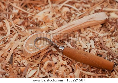 carving of a wooden spoon on wooden shavings background