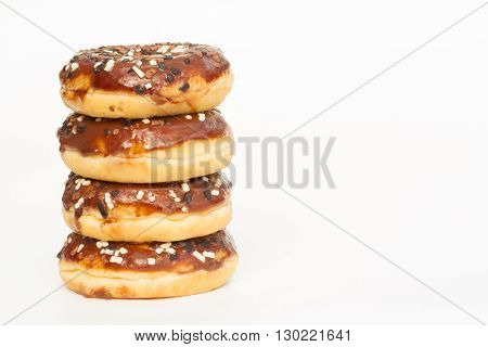A stack of donuts covered with chocolate icing and sprinkles on an isolated white background.