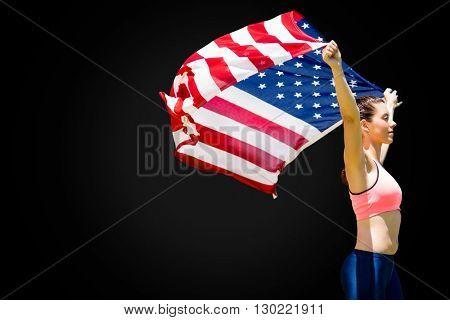 Profile view of sportswoman raising an american flag