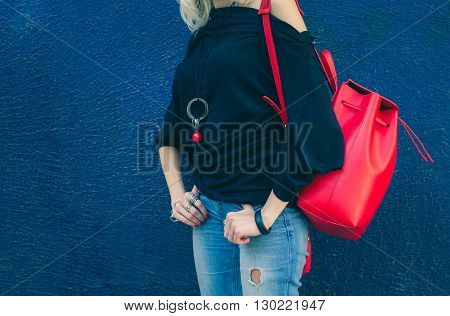 Fashionable beautiful big red backpack on the arm of the girl in a fashionable jeans, posing near the blue wall on a warm summer night. Warm color