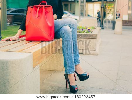 Girl in jeans and a fashionable high-heeled shoes sitting warm summer evening on the bench in the european city. Part of body. Warm color. Outdoor.