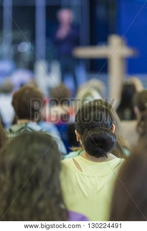 Conferences Concept and Ideas. Male Lecturer Explaining and Performing On Stage In front of the Large Group of People. Horizontal Image Composition