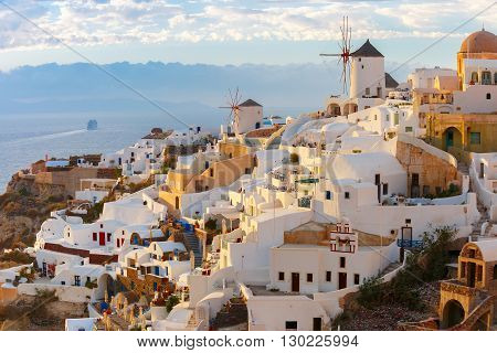 Picturesque famous view, Old Town of Oia or Ia on the island Santorini, white houses and windmills at sunset, Greece