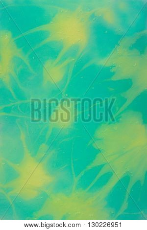 Abstract Yellow Splashes on the Turquoise Background Made with Paint Shampoo Glass and Paper