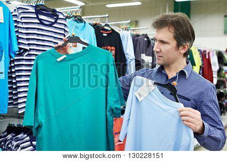 Man Chooses T-shirt In Store