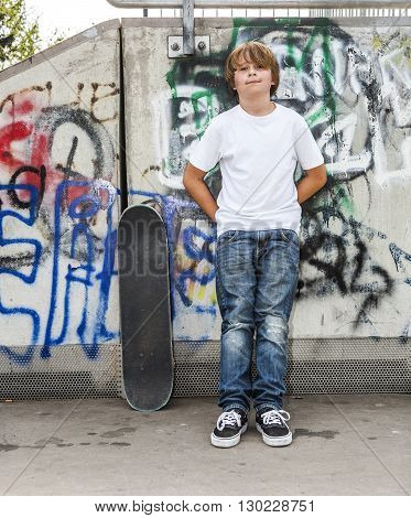 Boy Relaxes With His Skate Board At The Skate Park