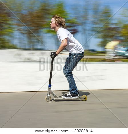Boy Has Fun Jumping With The Push Scooter At The Skate Park