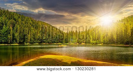 Lake Among The Forest In Mountains At Sunset