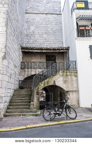 Old stone staircase with iron railings and vintage bicycle