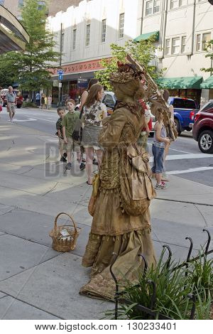 Asheville, North Carolina, USA - June 8, 2013: A woman costumed as a bronze female statue in Victorian dress with parasol remains motionless for tips by Woolworths in downtown Asheville as tourists pass by on June 8, 2013 in Asheville, NC