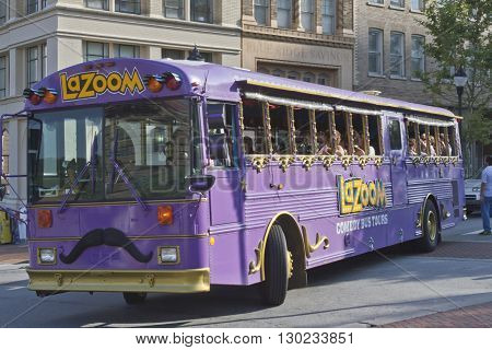 Ashville North Carolina USA - August 5 2013: The big purple LaZoom comedy tour bus packed with tourists drives through downtown Asheville on a summer day