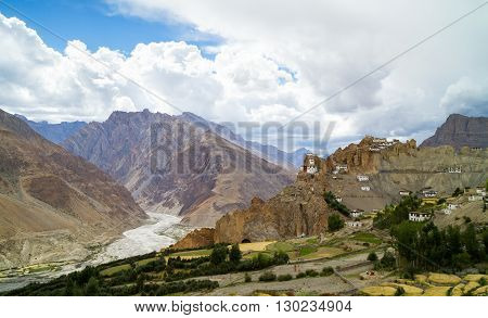 Panorama of the Dhankar monastery on the abrupt slopes of Himalayas Spiti river and nearby peasant fields in the Spiti valley (north India)