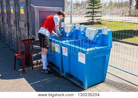 SAMARA RUSSIA - APRIL 24 2016: Unidentified athlete washes his hands in the mobile sink near the public toilets