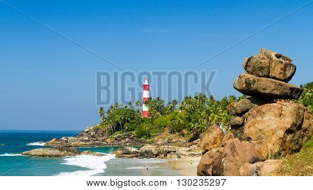 The lighthouse on the cape stretching into the Arabian Sea and beach with rocks in the foreground at a resort in Kerala in sunny weather (southern India)