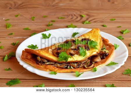 A delicious omelet with mushrooms, cheese and parsley. Stuffed omelet. Eggs recipe