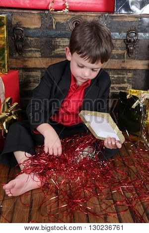 Little boy wearing a christmas suit looking at gifts