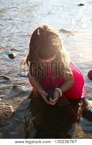 Little girl playing in a shallow stream of water