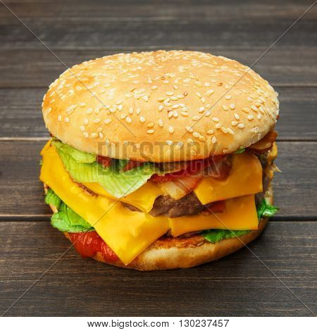 Classic american burger food. Big double cheese burger at wood. Hamburger with fresh vegetables and meat. Burger with cheese, beef, tomato, lettuce. Cheeseburger at rustic wooden background.