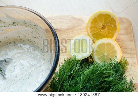 chopped lemon and sprigs of dill next to bowl of homemade mayonnaise