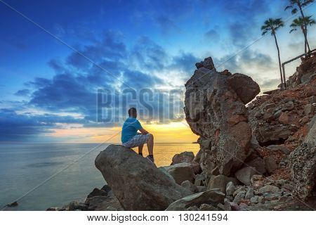 Man watching sunset over atlantic ocean at Gran Canaria island, Spain