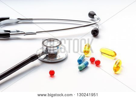 stethoscope on a white background with mix pills close up isolated