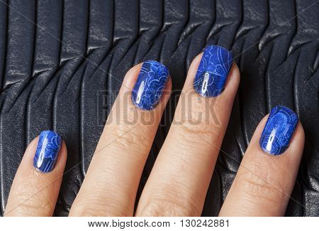 close up fingers with blue creative pattern manicure holding purse, indigo design, stylish fashion people concept