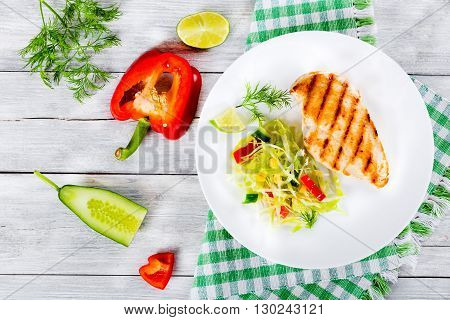 Healthy grilled chicken breast fillet with vegetables salad on a white dish on a wooden background studio light top view