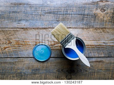 painting at home with can of blue paint  and brush on wooden background top view