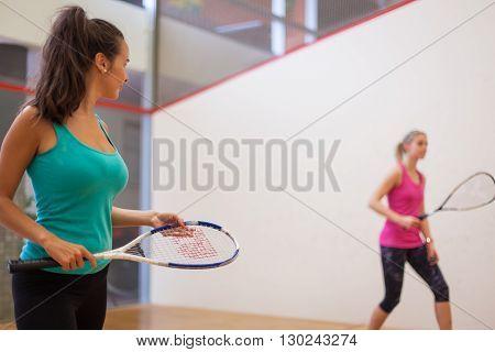 Young girls playing squash in squash court