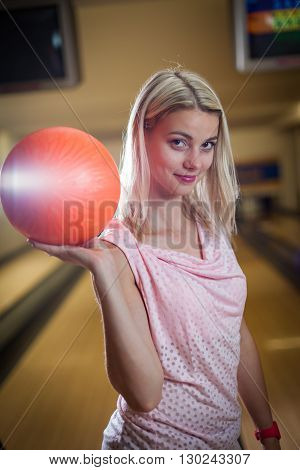 young lady at the bowling alley with the ball in hand getting ready for the game of bowling