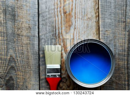 jar with blue paint and brush  with red grip on the wooden background top view close up