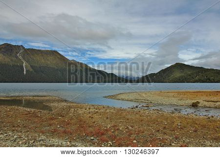 Landscape in the Fjordland National Park New Zealand. Green Lake and mountains.