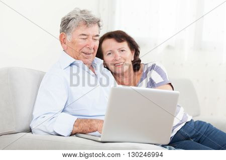 Senior couple laughing while using laptop at home