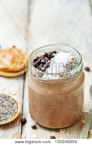 Chocolate Coconut Chia seeds overnight oats on a white wooden background.